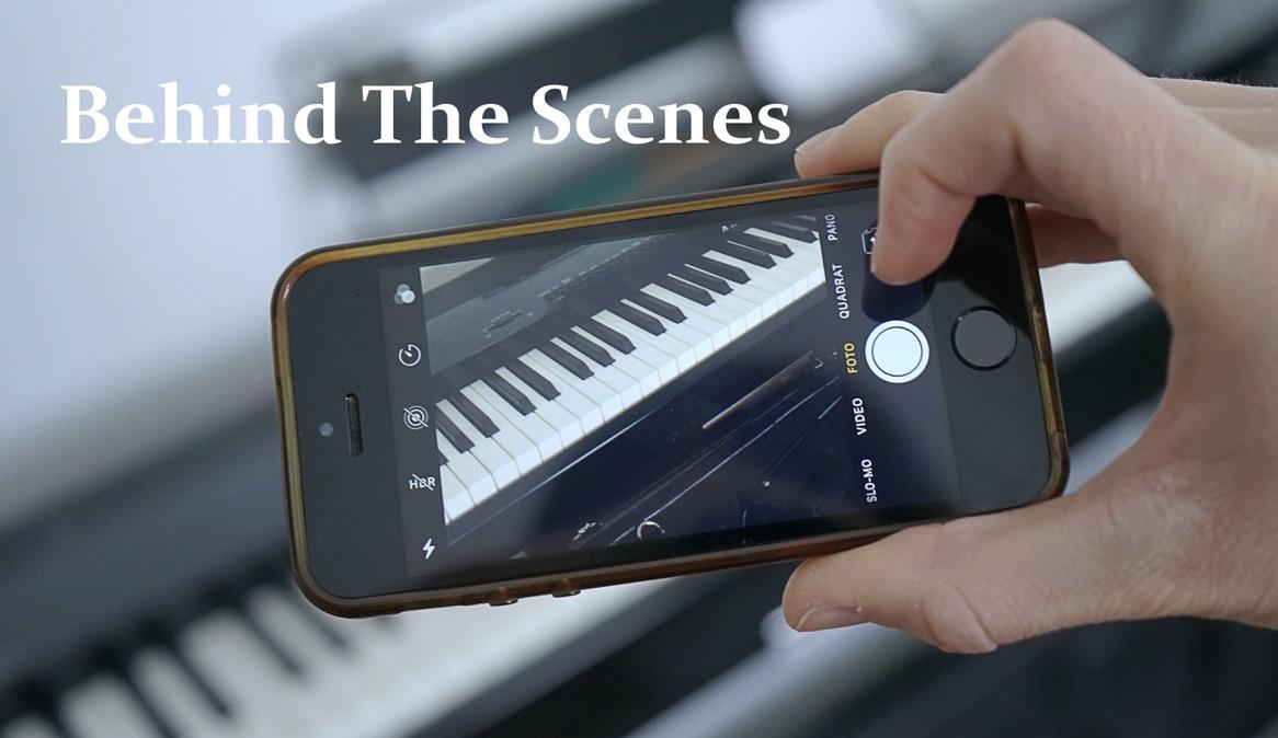 """Titelbild zum Format """"Behind The Scenes"""": Eine Hand hält ein Smartphone. Auf dem Bildschirm ist die Handykamera zu sehen, mit der gerade ein Klavier fotografiert wird."""