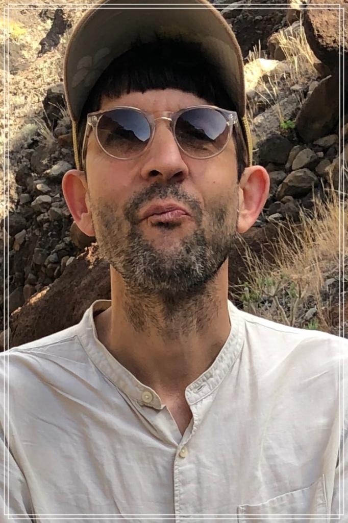 Porträtaufnahme Eric Eitel mit Cap, Sonnenbrille und weißem Hemd.