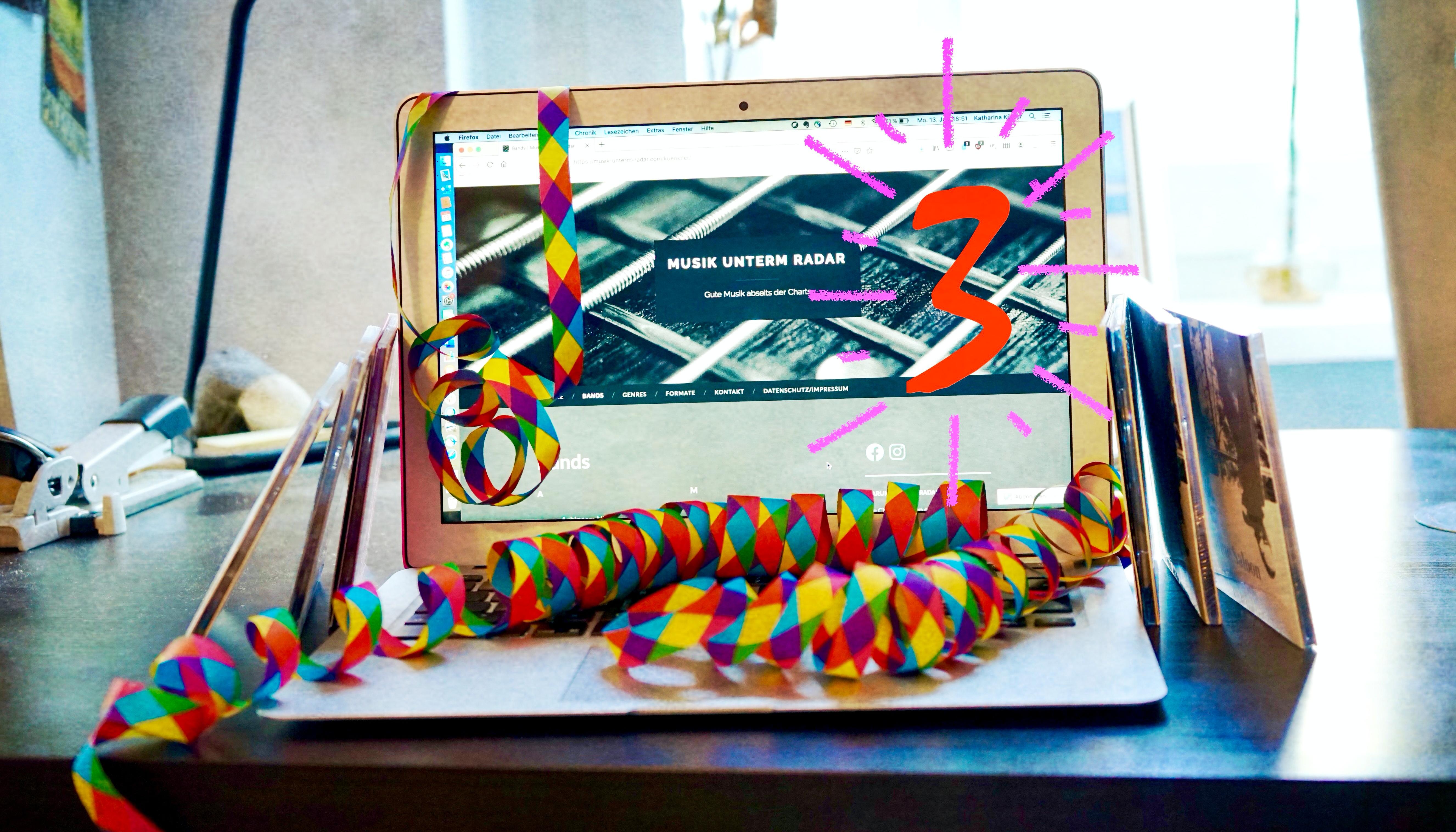Laptop mit Luftschlangen und sechs CDs. Der Bildschirm zeigt die Website Musik unterm Radar und die Zahl drei zum dreijährigen Jubiläum.
