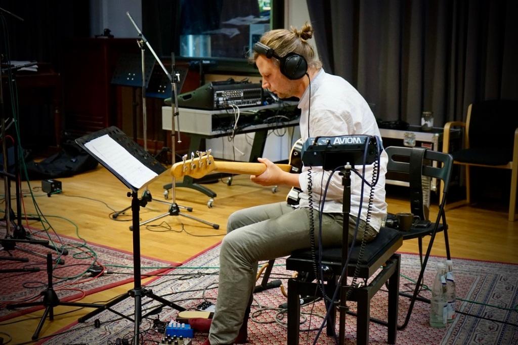 Bassist mit Kopfhörern im Studio